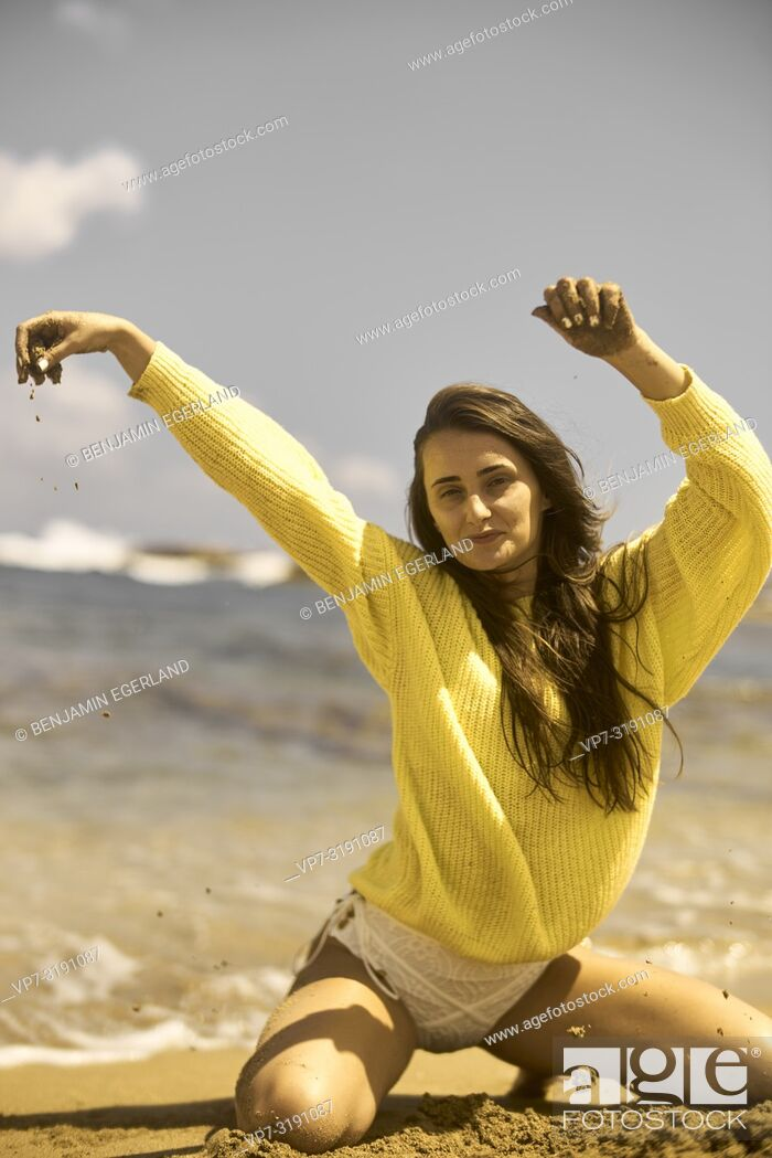 Photo de stock: Portrait of woman at the beach, wearing a yellow sweater. Crete, Greece.
