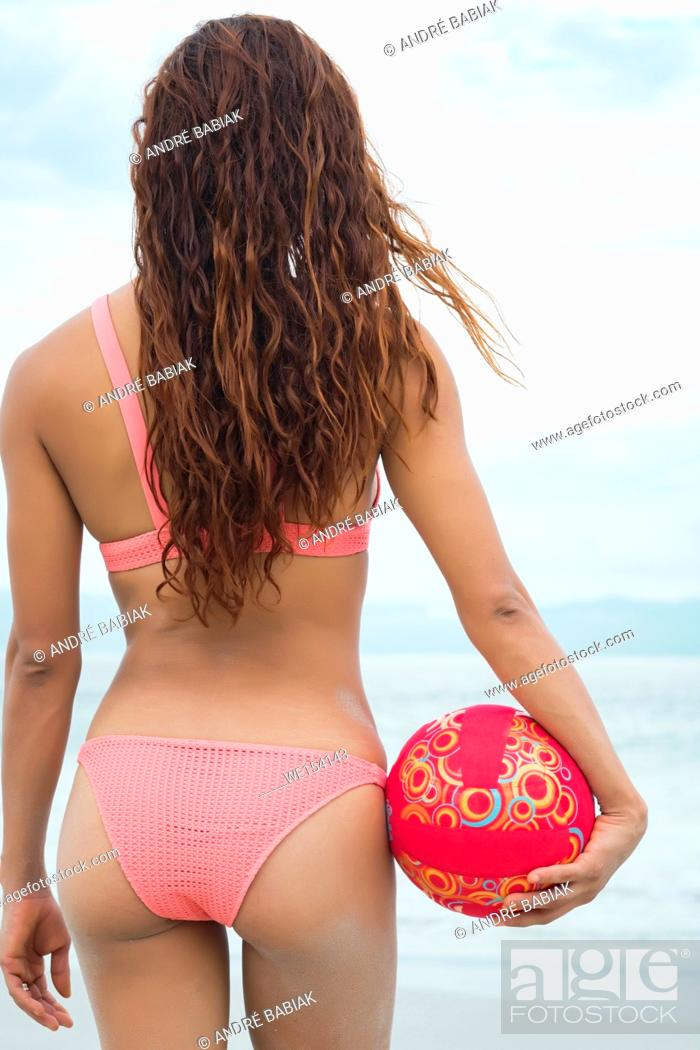 Stock Photo: Backside of attractive woman in bikini holding a volleyball at a beach.