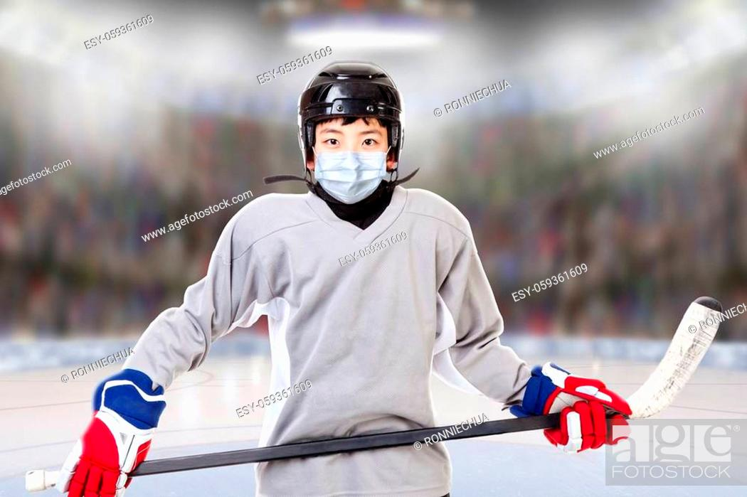 Stock Photo: Junior ice hockey player with full equipment and sports uniform posing in fictitious arena with face mask. Concept of new normal in sports to prevent against.