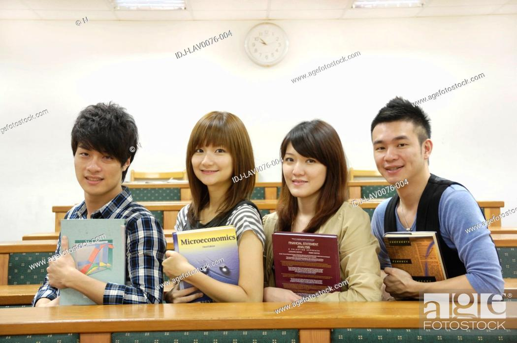 Stock Photo: University students holding books and smiling in a classroom.
