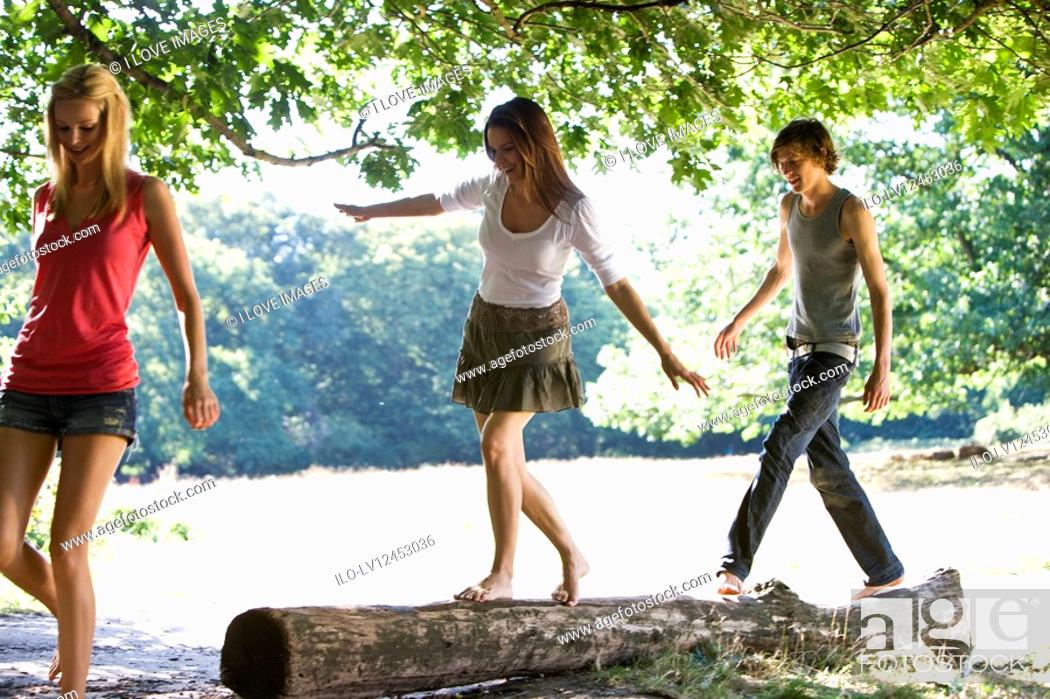 Stock Photo: Three young people in a park, two balancing on a log.