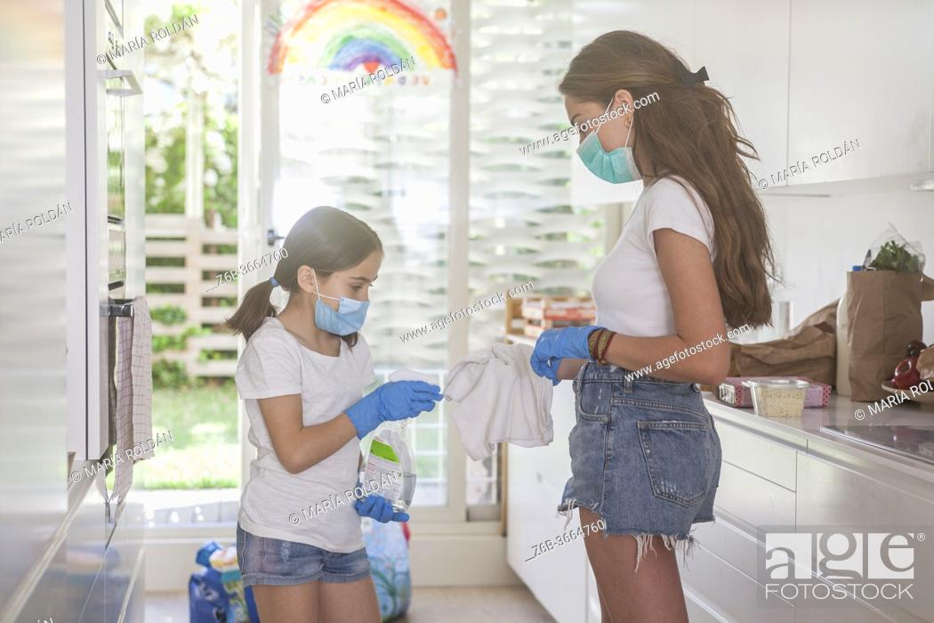 Stock Photo: mom and daughter wearing masks and gloves with cleaner.