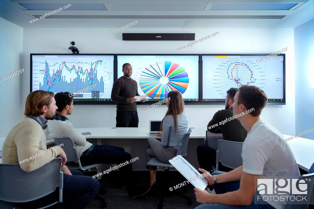 Stock Photo: Teacher with class of apprentices studying graphical screen display in railway engineering facility.