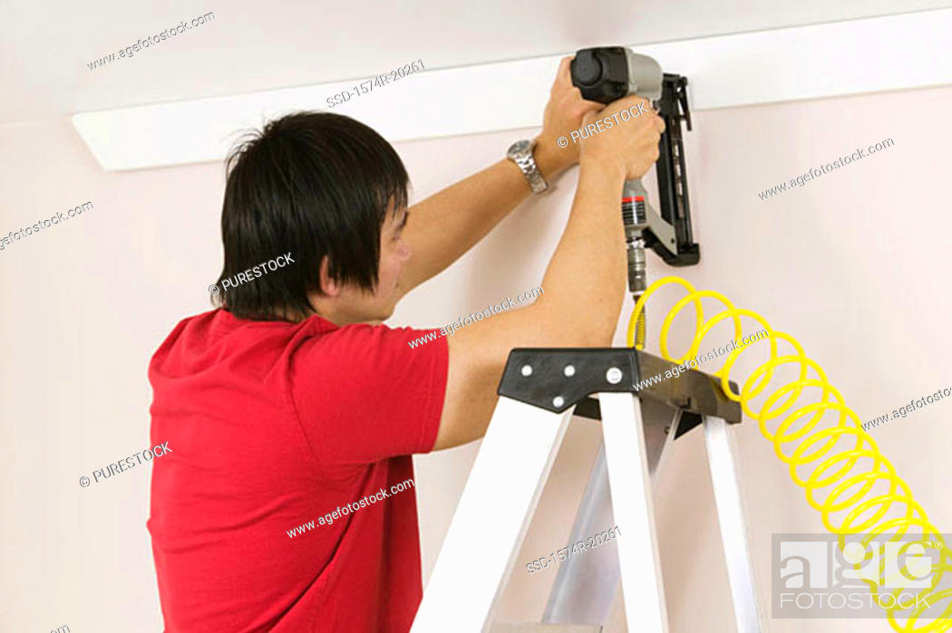 Stock Photo: Rear view of a young man using a drill on a wall.