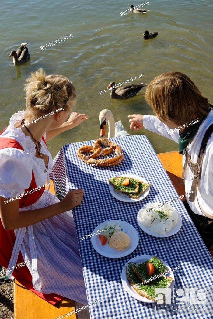 Stock Photo: Young couple in traditional Bavarian outfit, feeding swan in beer garden, Munich.