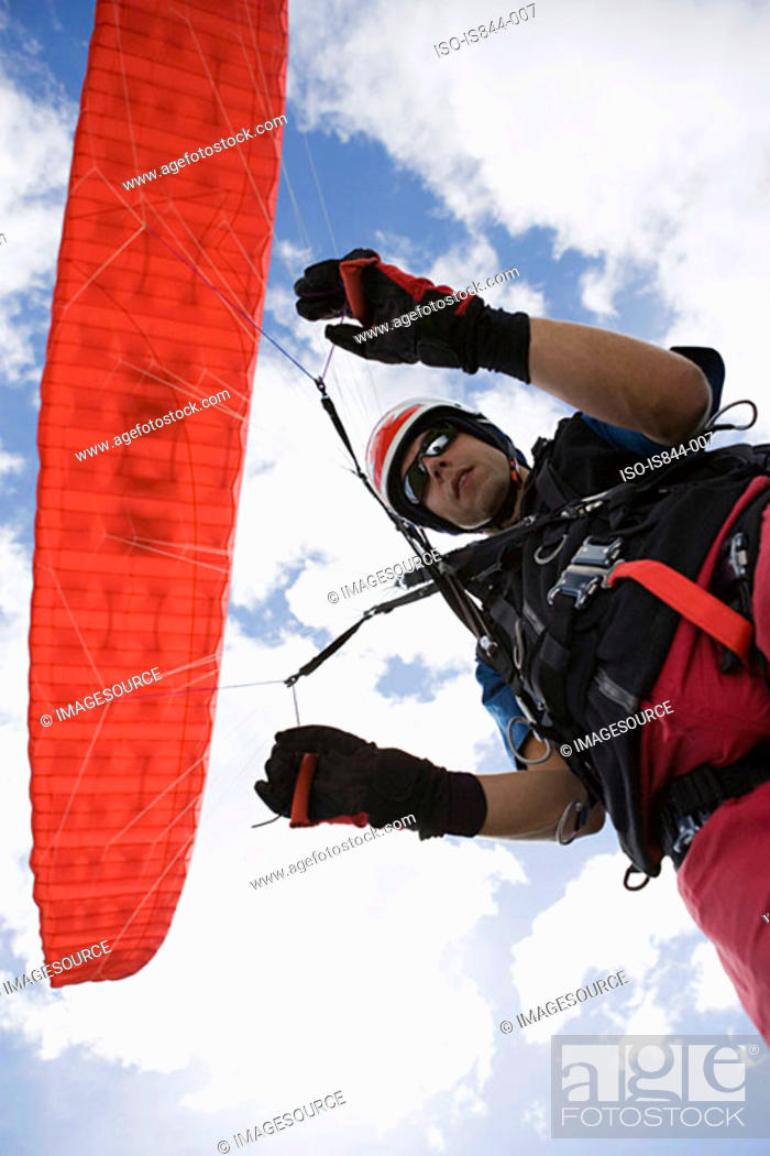 Stock Photo: Male parachutist with red parachute.