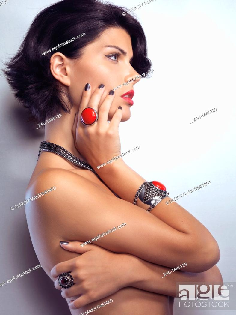 Stock Photo: Beauty portrait of a young glamorous woman wearing jewellery with red stones.