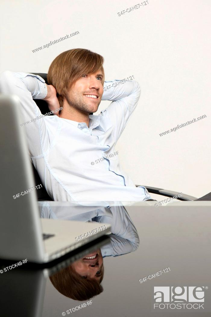 Stock Photo: Content businessman at desk leaning back.