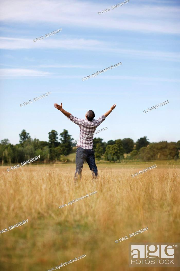 Stock Photo: Man with arms outstretched in rural field.