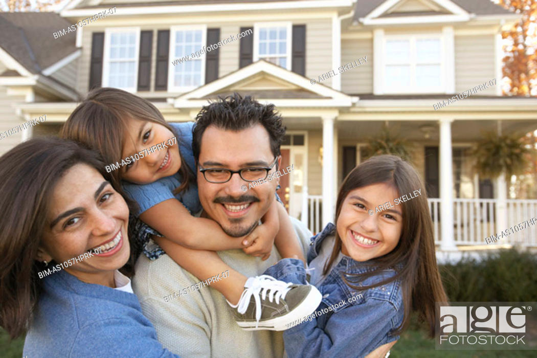 Stock Photo: Portrait of family standing in front of house.