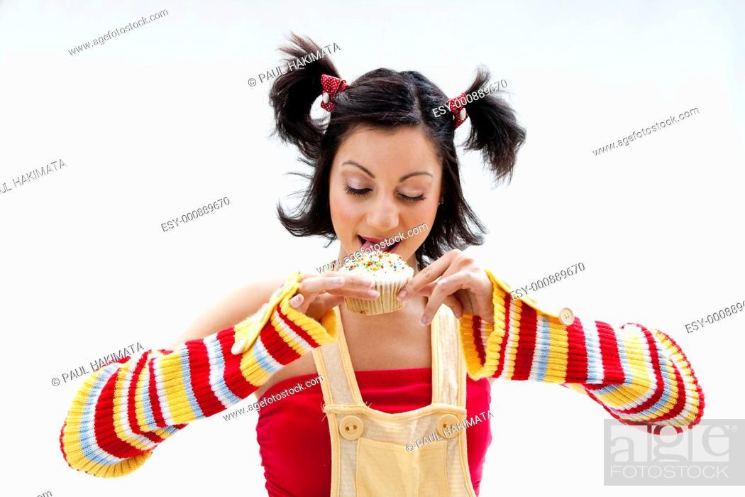 Stock Photo: Beautiful Latina girl licking a cupcake, isolated.