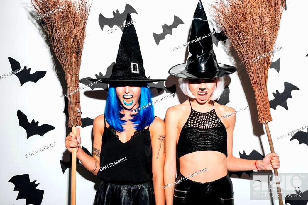 Stock Photo: Image of two emotional young women in halloween costumes on party over white background with brooms. Looking camera.