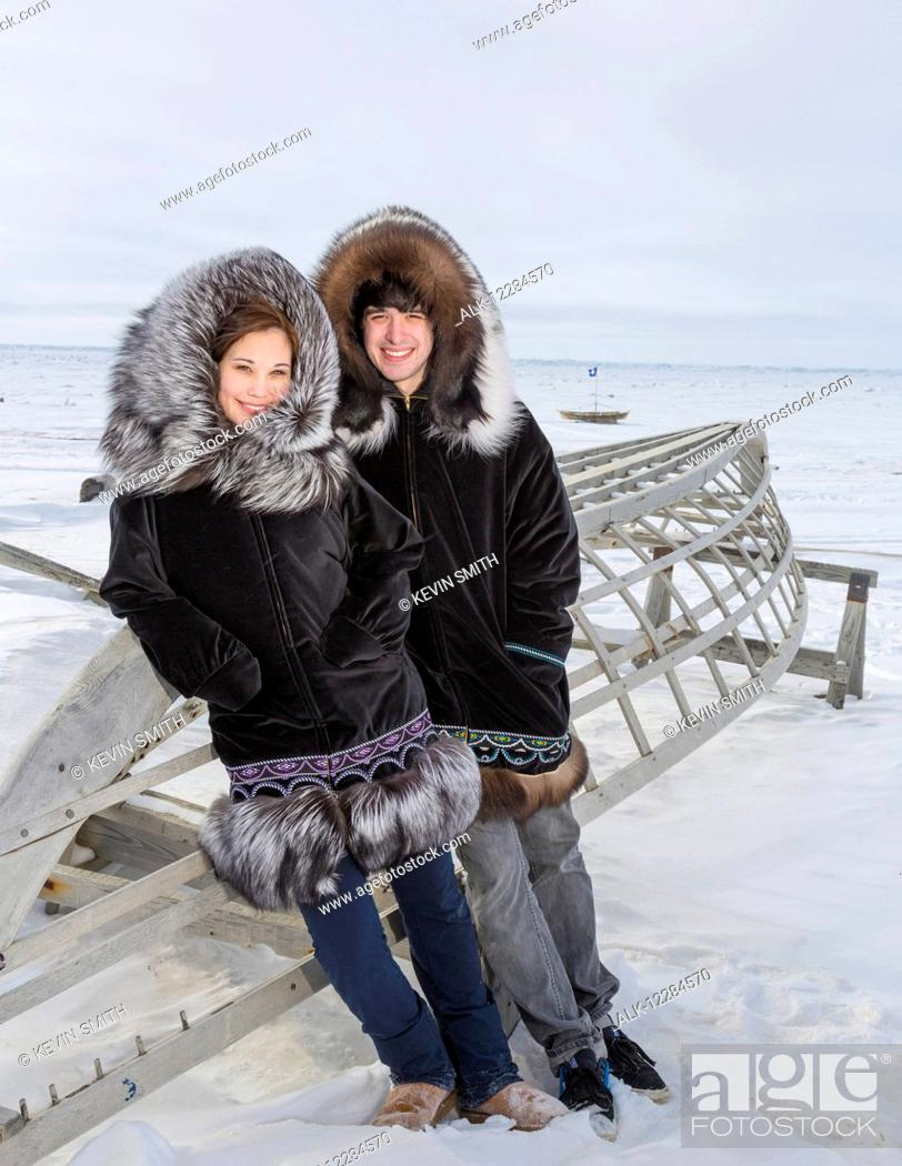 Imagen: Male and female native youths wear traditional fur parkas while standing next to a boat frame, Barrow, North Slope, Arctic Alaska, USA, Winter,.