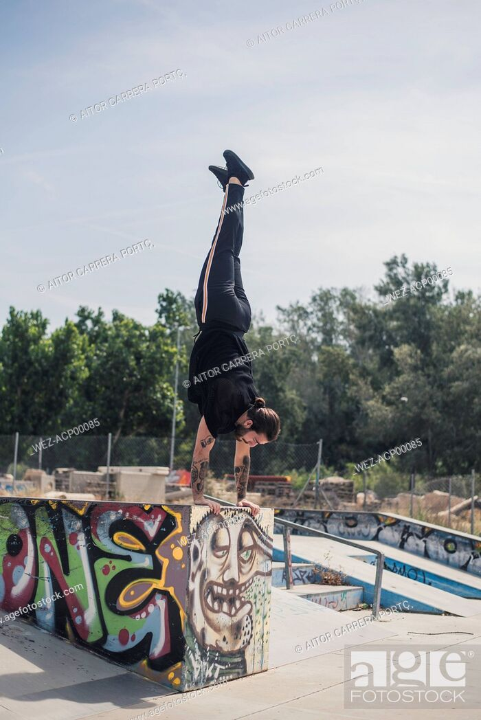 Imagen: Tattooed man doing handstand in a skatepark.