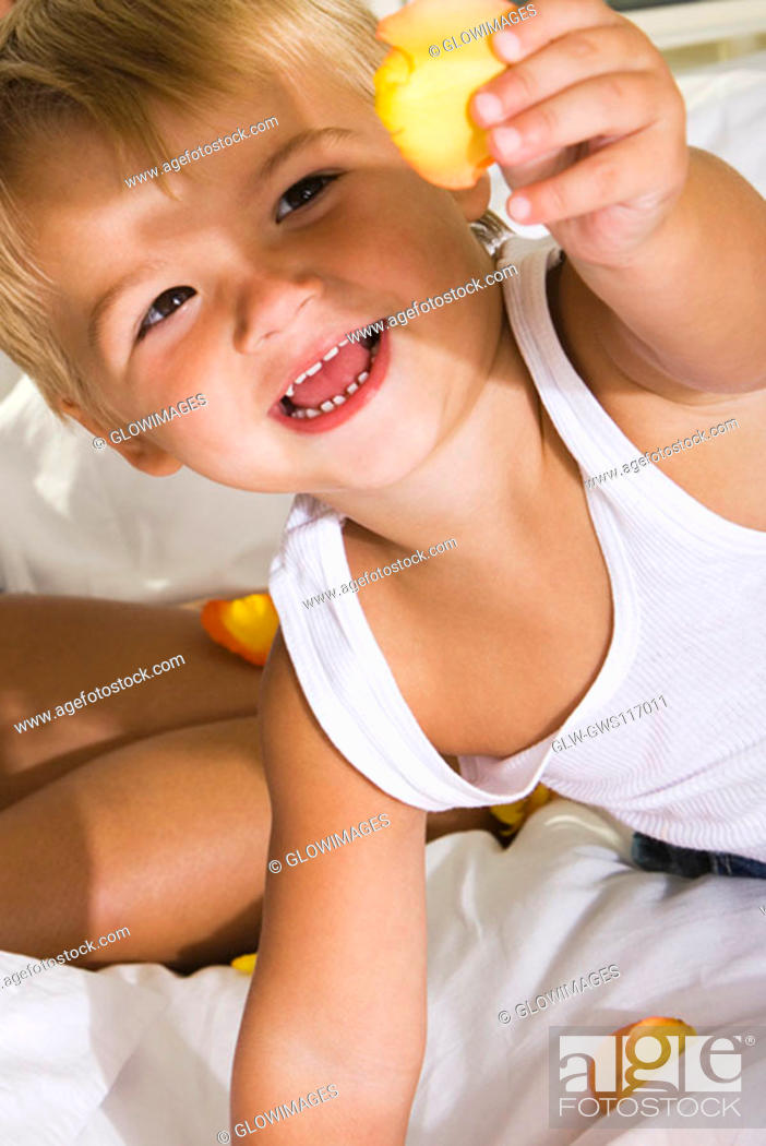 Stock Photo: High angle view of a boy holding a rose petal laughing.