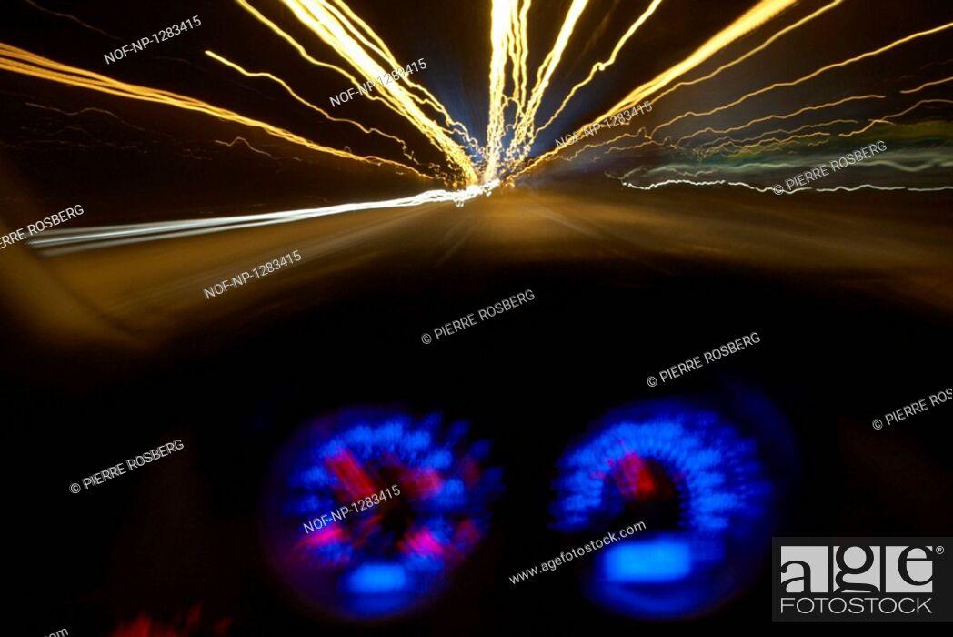 Stock Photo: A car driving at night.