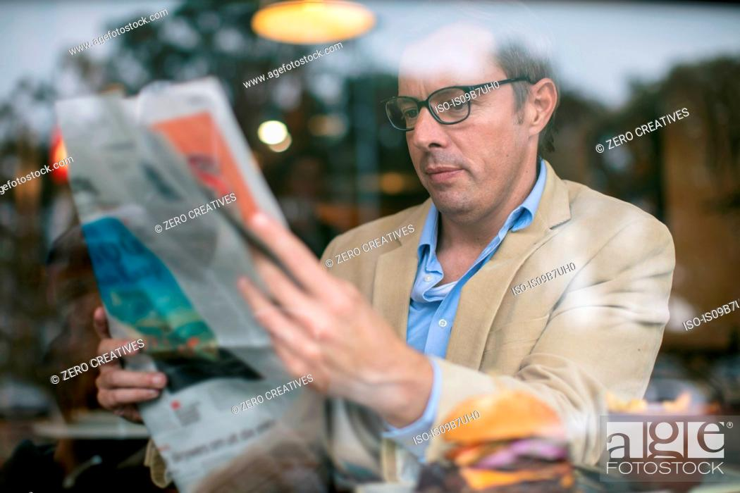 Stock Photo: Man in coffee shop reading newspaper.