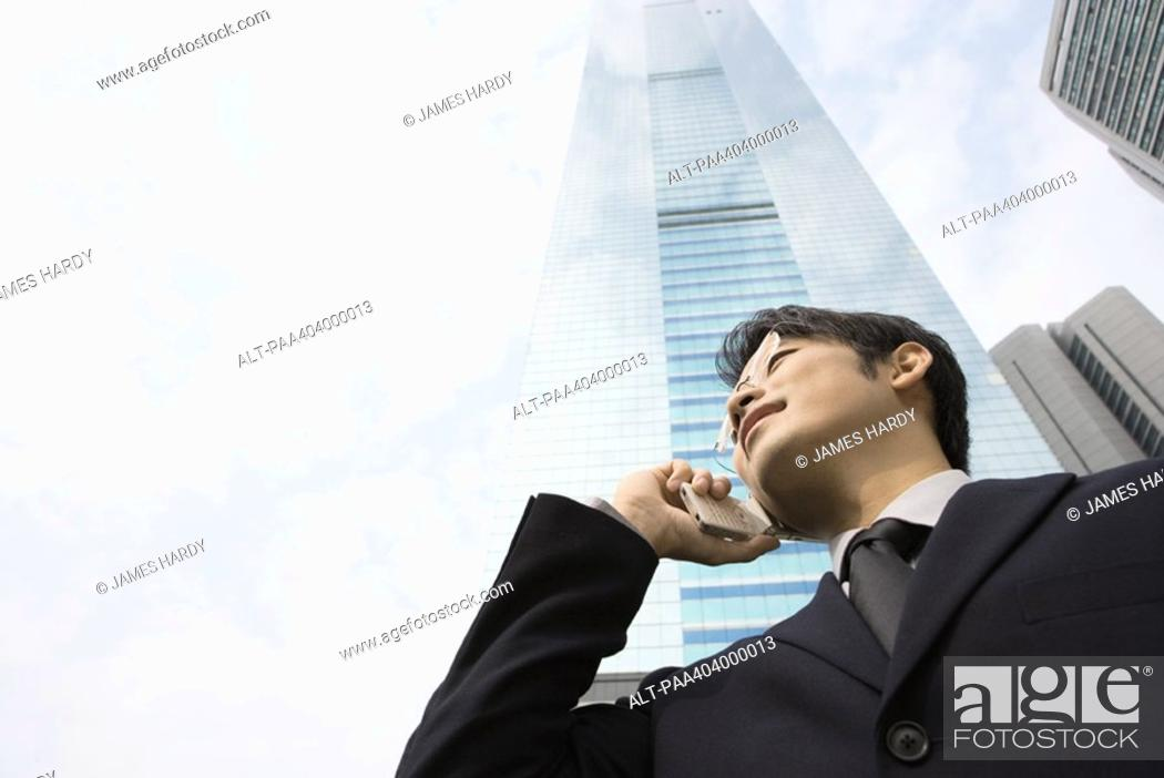 Stock Photo: Young businessman using cell phone, skyscraper in background, low angle view.