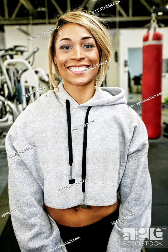 Stock Photo: Smiling Mixed Race woman posing in gymnasium.