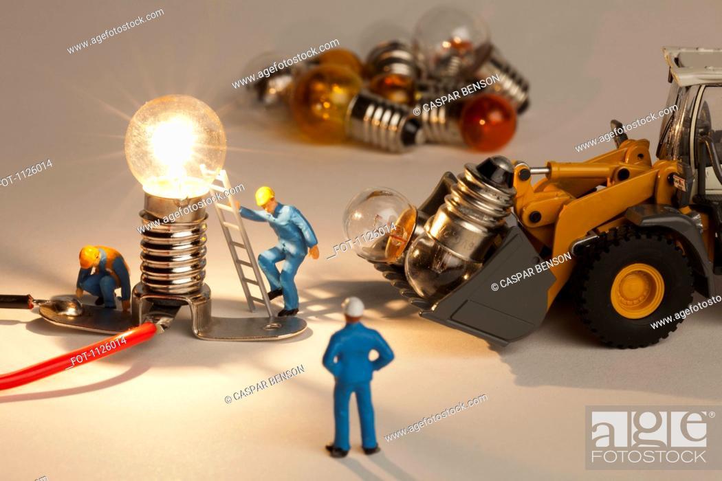 Stock Photo: Miniature electrician figurines working on an illuminated light bulb.