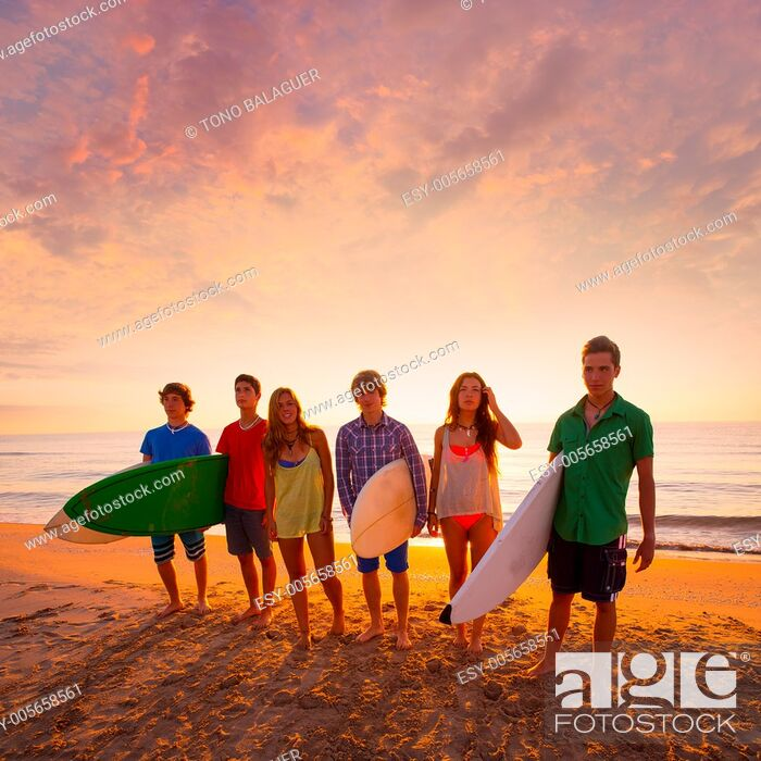 Stock Photo: Surfers teen boys and girls group walking on beach at sunshine sunset backlight.