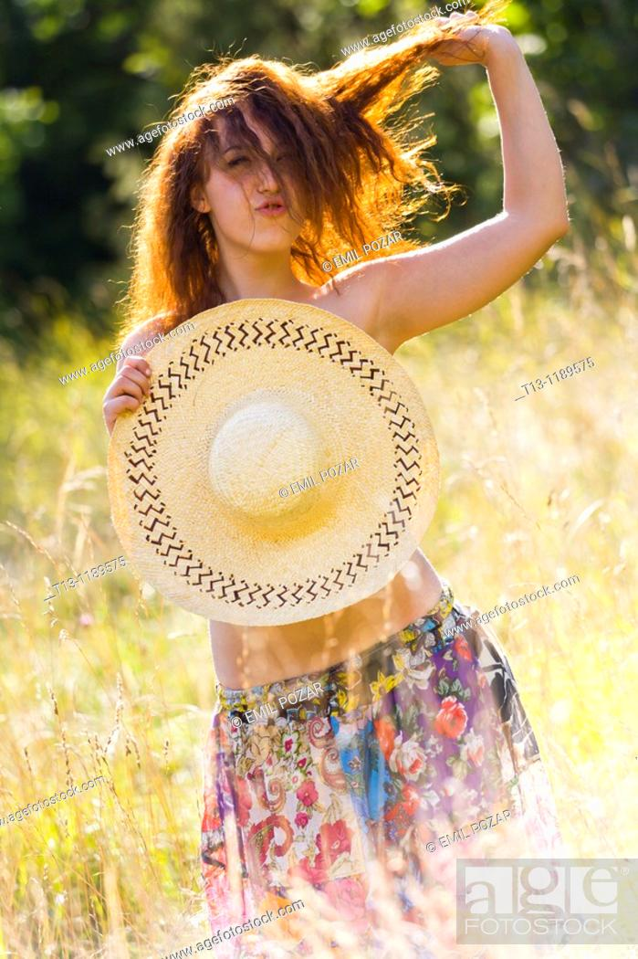 Stock Photo: Provocative young woman is standing in the grass field, pulling hair.