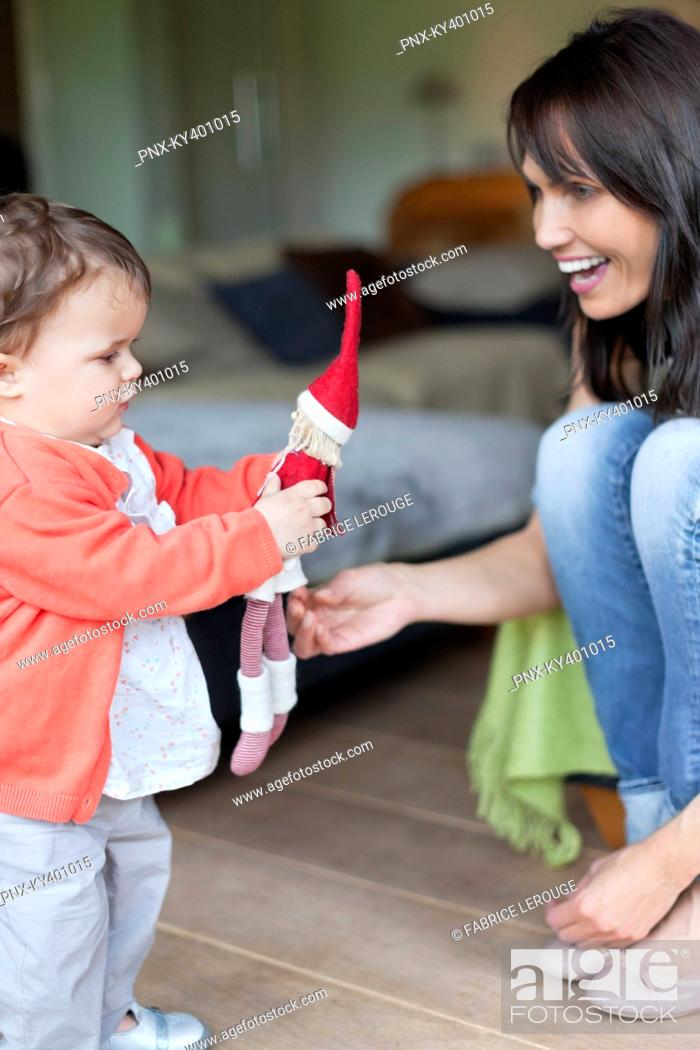 Stock Photo: Woman looking at her granddaughter playing with a toy.