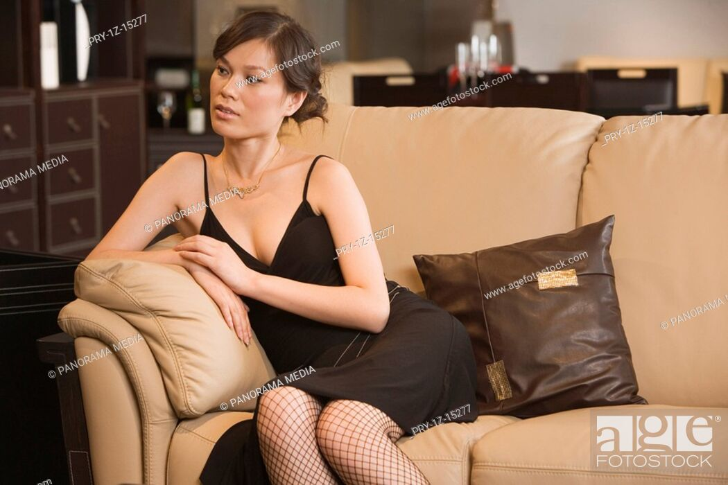 Imagen: Young woman sitting on sofa.
