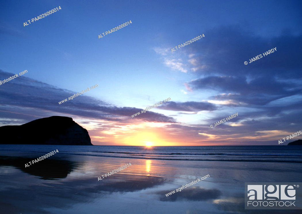 Stock Photo: New Zealand, Mahia Beach, ocean sunset with cliff in background.