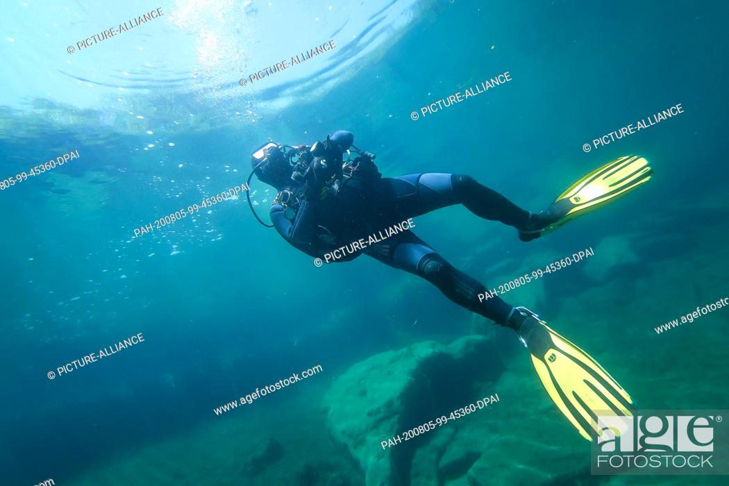Stock Photo: 31 July 2020, Lower Saxony, Hemmoor: Oude Egbrink dives in the chalk lake. The lake in the district of Cuxhaven is also popular with divers nationwide.