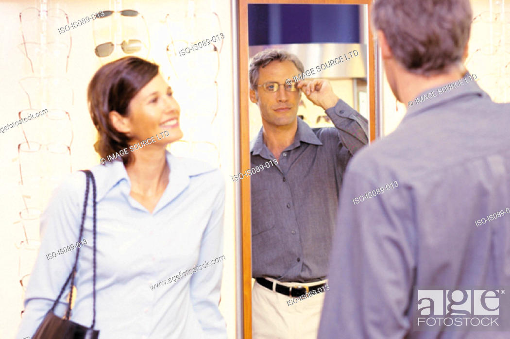 Stock Photo: Man and woman choosing spectacles.