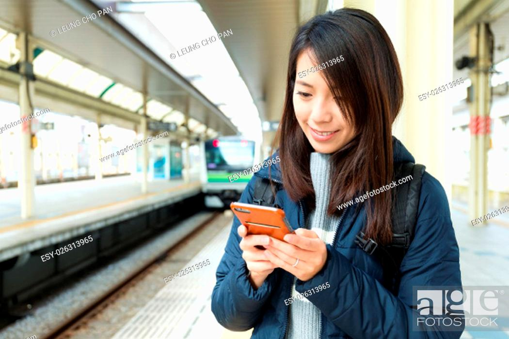 Stock Photo: Woman texting message on cellphone in train station.