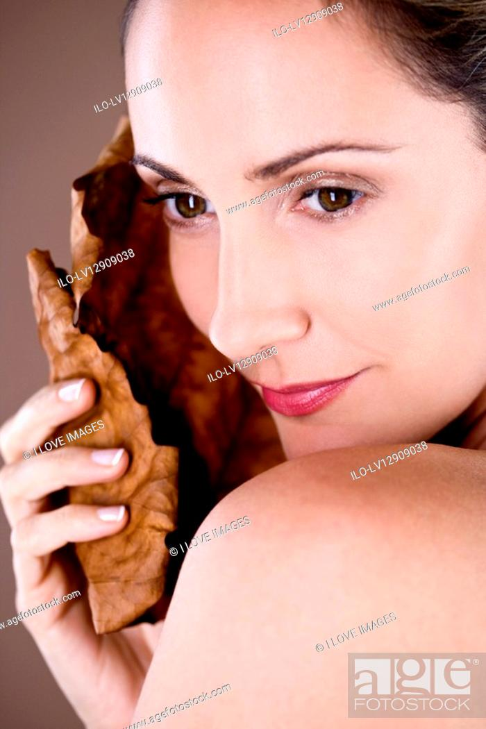 Stock Photo: Portrait of a mid adult woman holding a dried leaf.