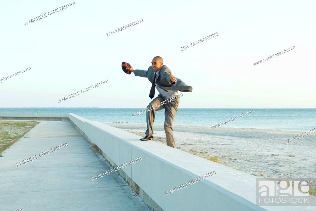 Stock Photo: Businessman standing on low wall at the beach, arms out, holding football.