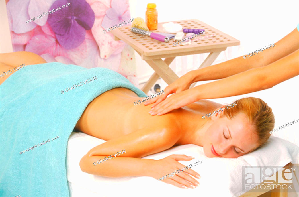 Stock Photo: Young woman getting a massage from a masseuse.