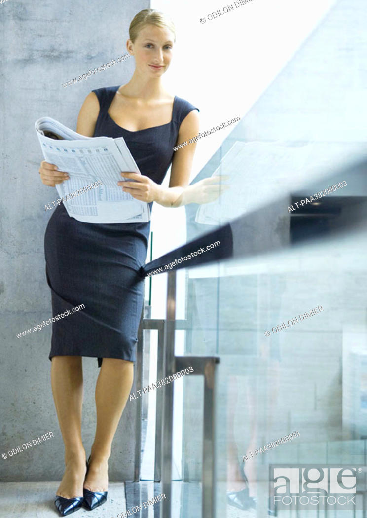 Stock Photo: Businesswoman leaning on railing, smiling at camera, full length.