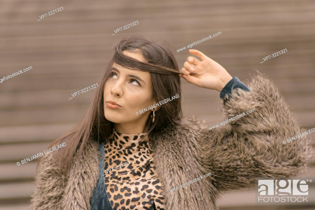 Stock Photo: portrait of playful woman curling lips and looking up to styled hairs, new hair cut, curious emotion, in Munich, Germany.