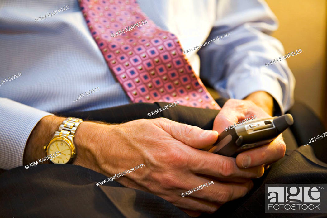 Stock Photo: TEXAS  Austin   Male executive enter text using keypad on cellular telephone while working in hotel room, left handed, watch.