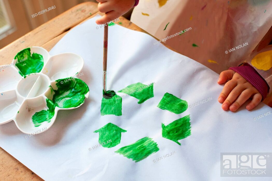 Stock Photo: Child painting green recycling symbol.