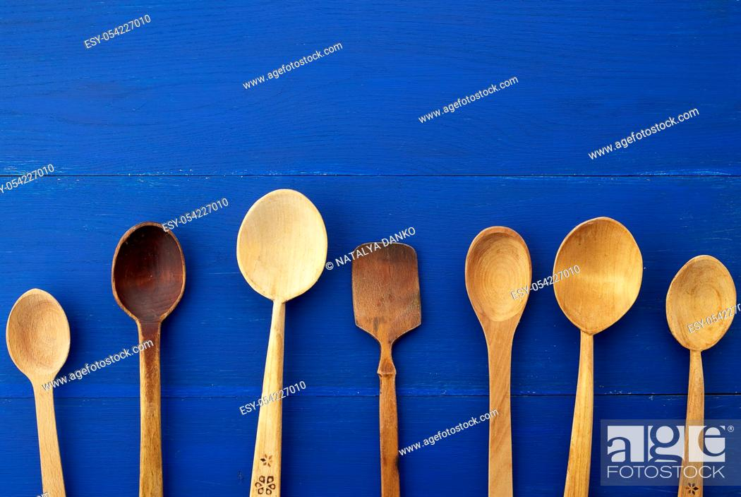 Stock Photo: set of yellow wooden vintage spoons on a blue wooden background, top view, copy space. Household equipment. Kitchen utensil.