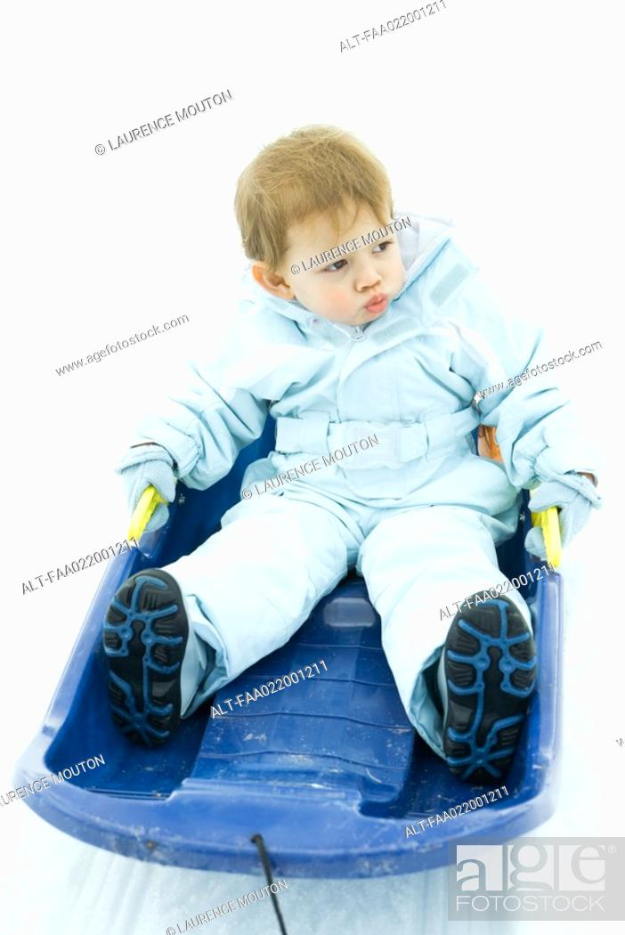 Stock Photo: Little boy sitting on sled, looking away, frowning.