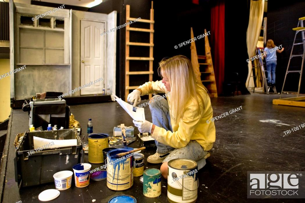 Photo de stock: A high school student studies paint color samples while building the set of a play in her school's theatre. Stagecraft is an elective course at the school.