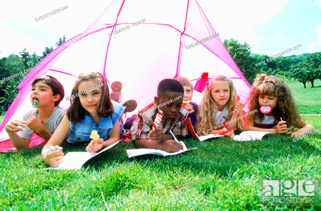 Stock Photo: Young children sketching under a tent.