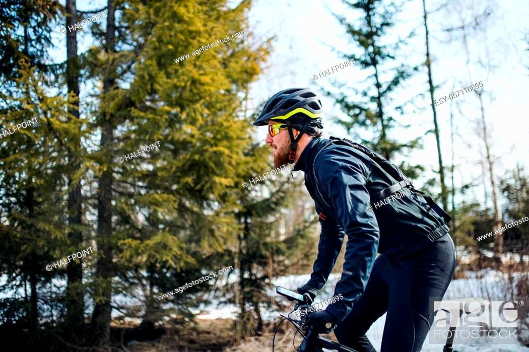 Stock Photo: A side view of mountain biker riding in snow outdoors in winter nature.