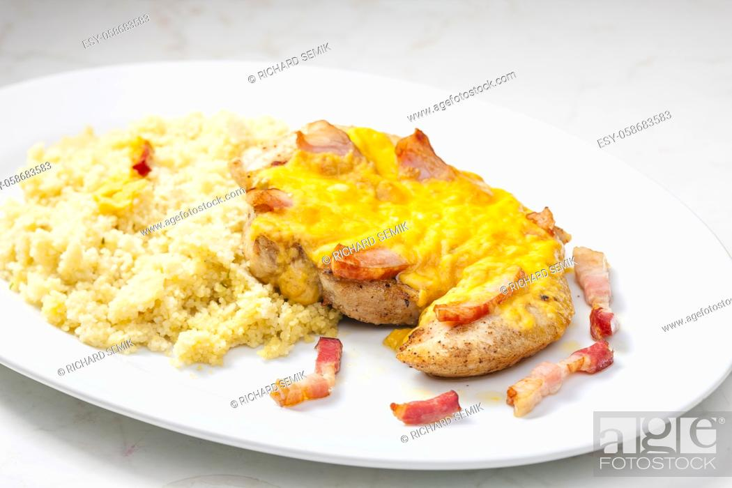 Imagen: poultry meat baked with bacon and cheese served with couscous.