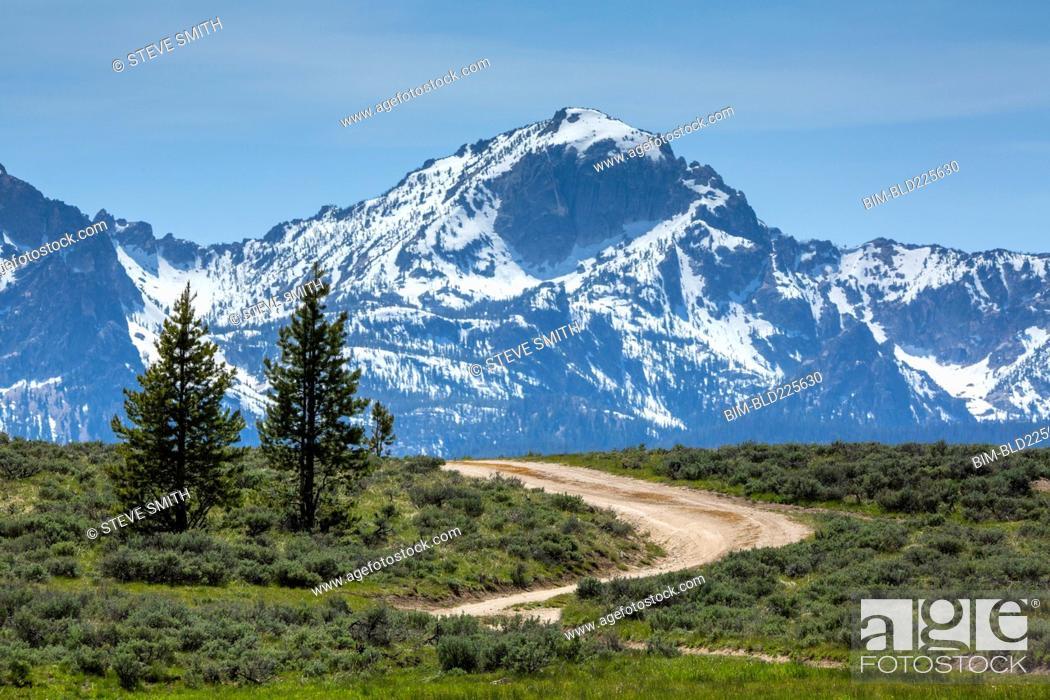 Stock Photo: Winding dirt road near snow covered mountain range.