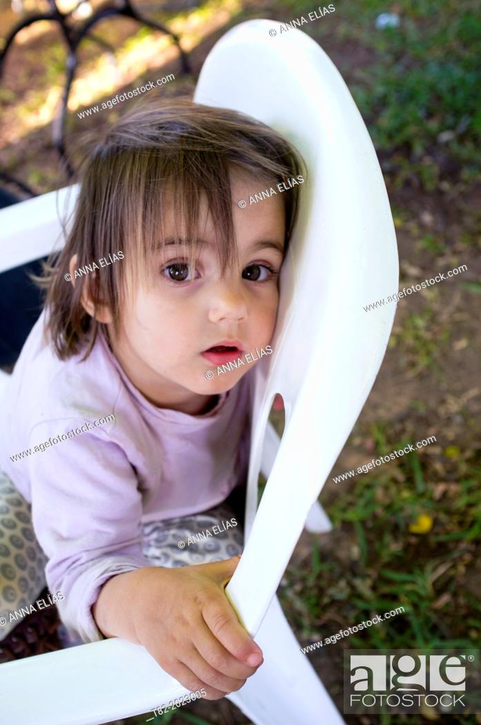 Stock Photo: Face of 2 year old girl reclining on a chair looking at camera spit. Sevilla, Andalucia, Spain, Europe.