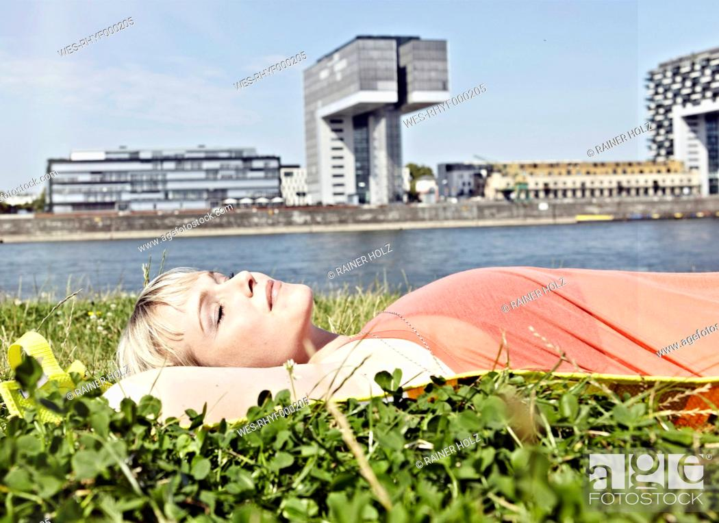 Stock Photo: Germany, Cologne, Young woman relaxing in grass.
