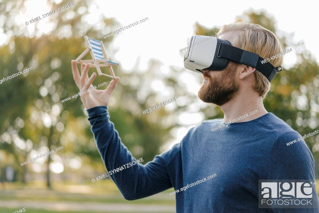 Stock Photo: Man in autumnal park wearing Virtual Reality Glasses looking at miniature beach lounger.