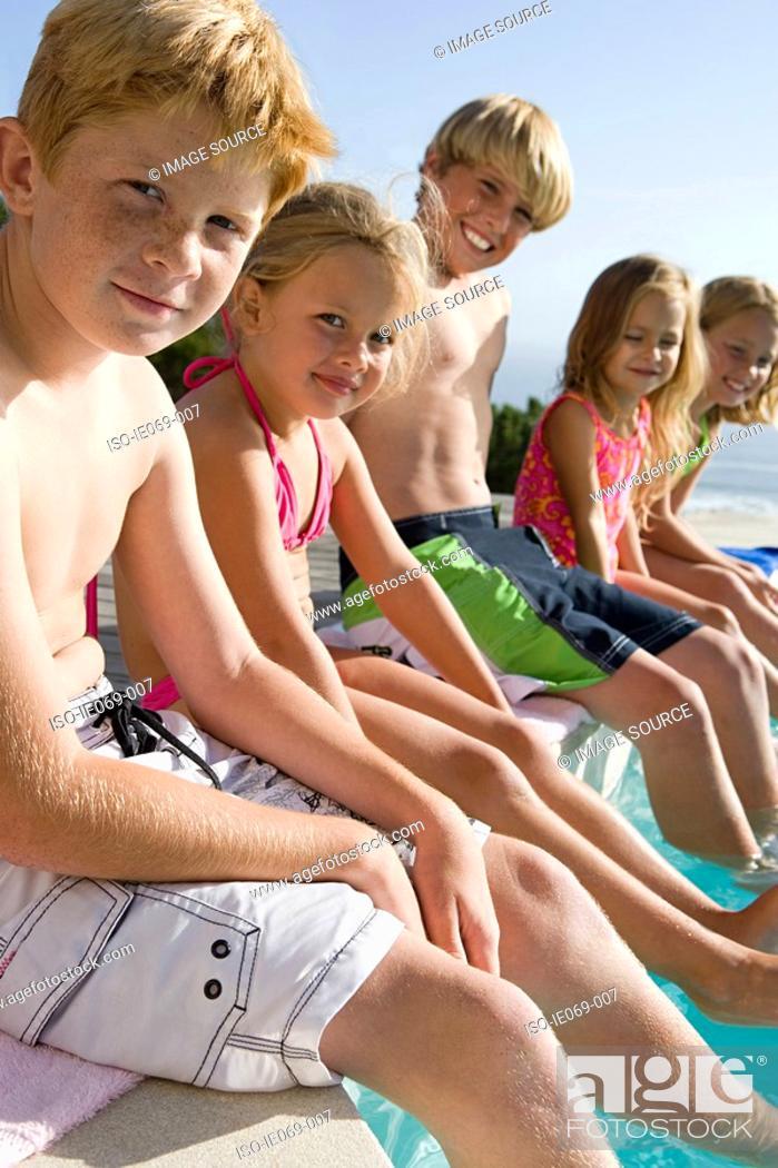 Stock Photo: Kids sitting on edge of swimming pool.